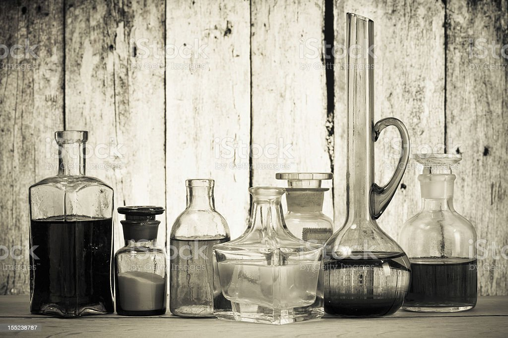 Antique glass bottles and in front of wooden background stock photo