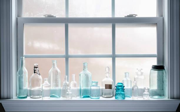 Antique glass bottles on a windowsill stock photo