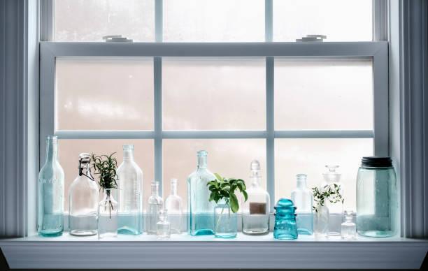 Antique Glass Bottles on Windowsill stock photo