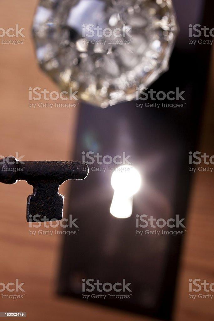 antique glass door knob and skeleton key light in keyhole royaltyfree stock photo