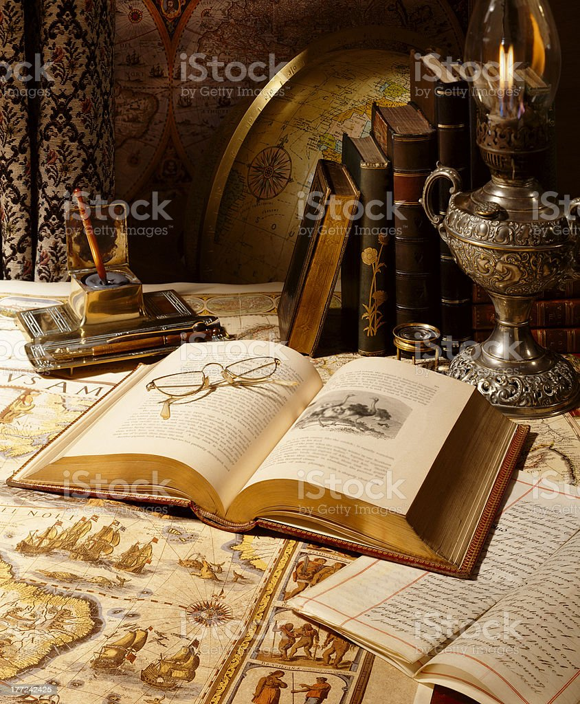Antique globe with maps, books and lamp in room setting royalty-free stock photo