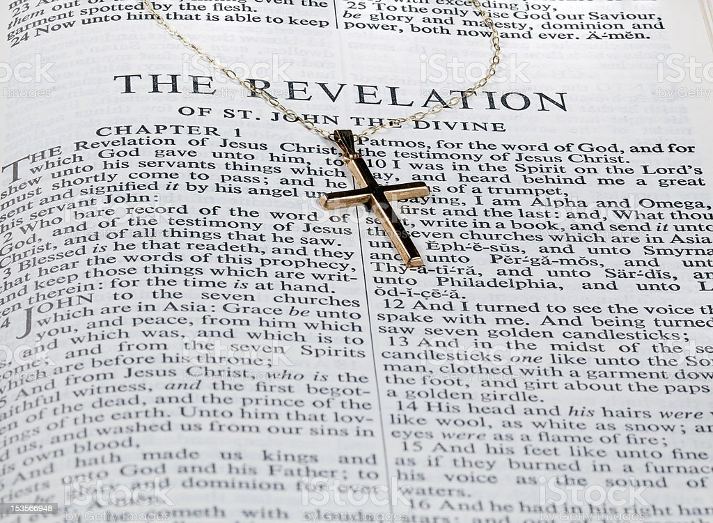 Antique gold cross on page of bible stock photo