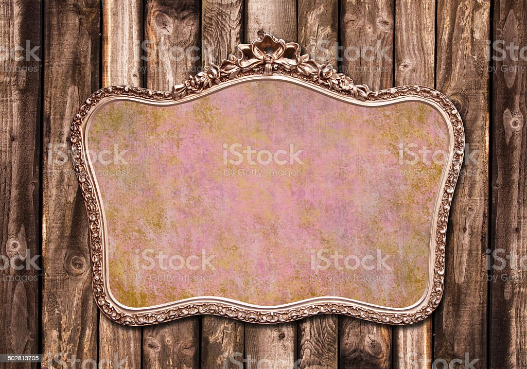Antique golden frame hanging on a wooden wall royalty-free stock photo
