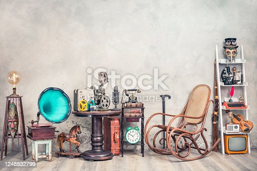 istock Antique gramophone, rocking chair, old typewriter, retro radio, tape recorder, projector, books, clock, camera, fiddle, mask, cylinder hat, cane, suitcase, bow. Vintage style filtered photo 1248832799