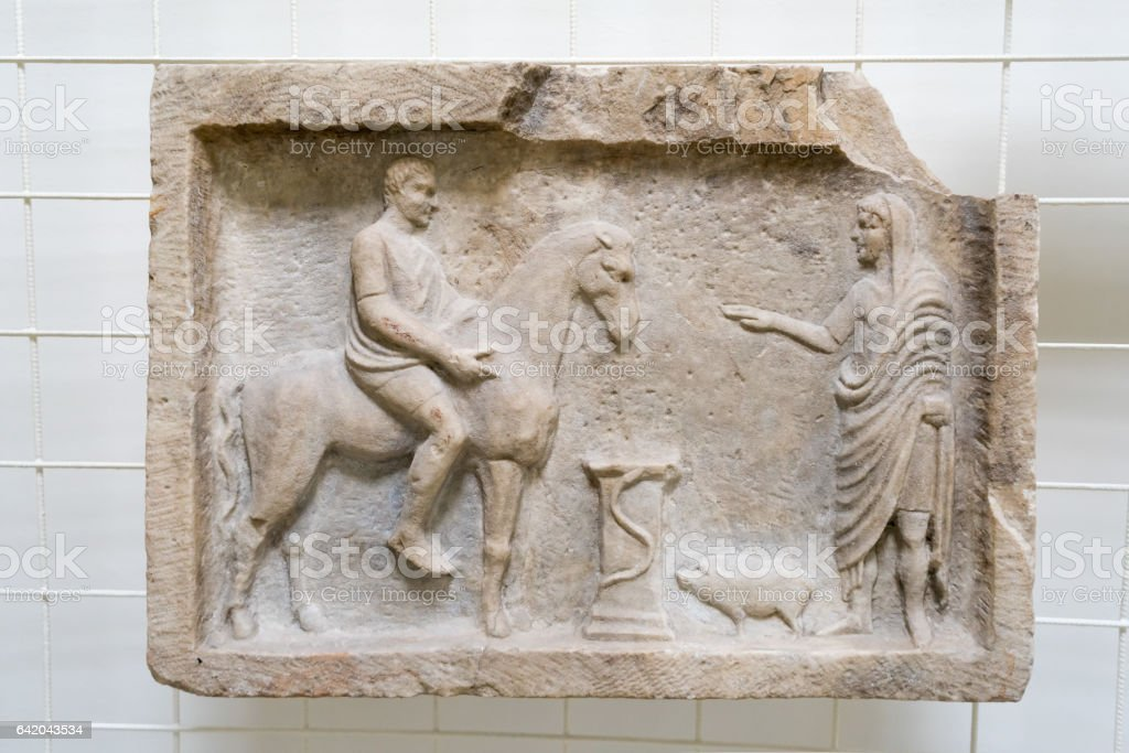 Antique Greek bas-relief with people fragment on desk stock photo