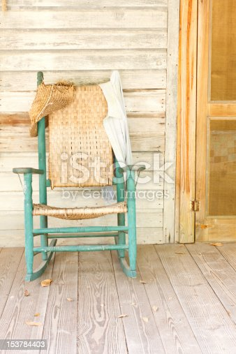 A vintage green rocking chair in a rural setting on the front porch of an old farmhouse.