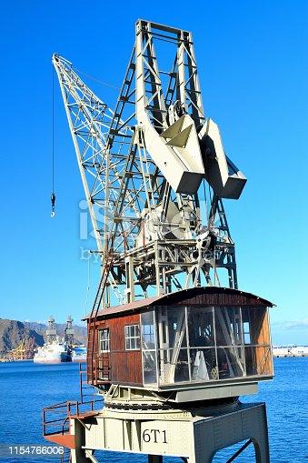 Antique harbor crane with sunlight