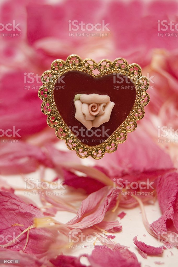 Antique Heart Brooch and Pink Petals royalty-free stock photo