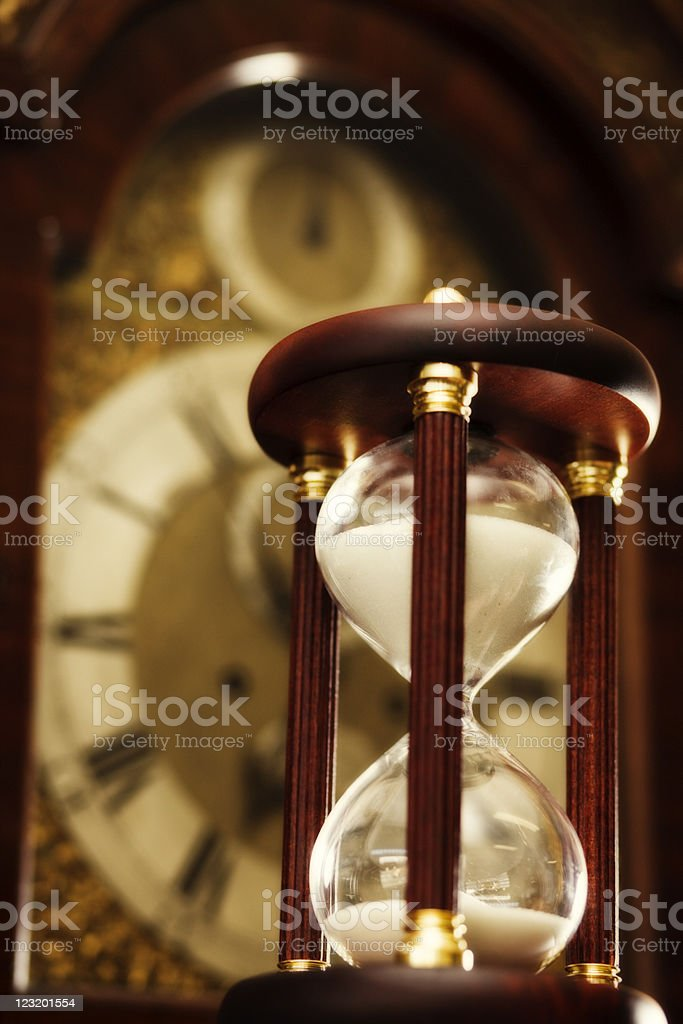 Antique hourglass with grandfather clock face in background. royalty-free stock photo