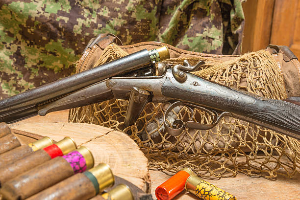 Antique hunting gun, hunting belt with cartridges Old hunting gun, hunting belt with cartridges, hunting bag, stump of tree on a wooden background gun shop stock pictures, royalty-free photos & images
