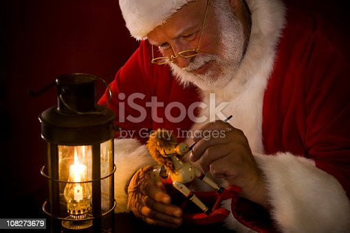 Santa Claus painting a toy by a lit lantern. Edited for classic, film-like feel. CLICK FOR SIMILAR IMAGES OR LIGHTBOX WITH MORE SEASONAL IMAGES.