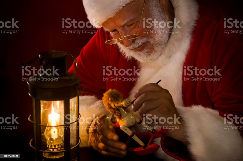 Antique Image of Santa Claus Painting Toy by Lantern Light stock photo