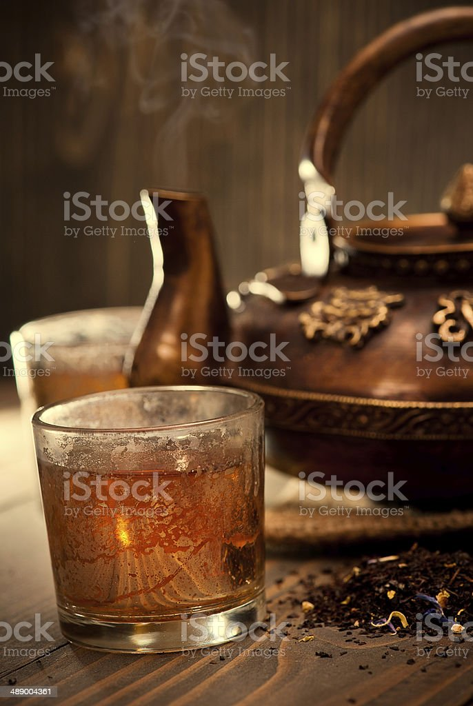 Antique iron hot tea pot on dark wooden background stock photo
