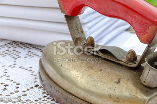 istock Antique iron with stack of linen clothes 589428662