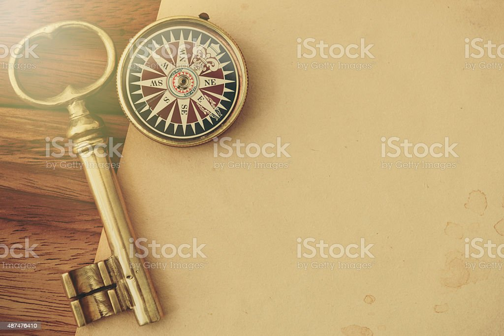 Antique Key and Compass on a Wooden Desk stock photo