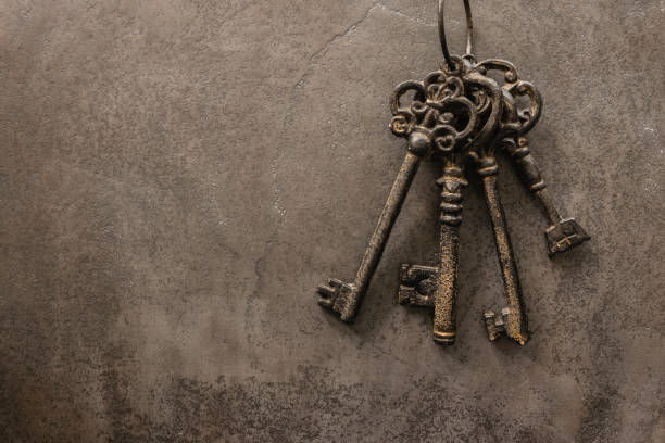 antique keys on old steel metal texture background - key stock pictures, royalty-free photos & images