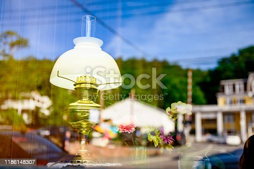 This is a photograph of an antique lamp on retail display in a small, rural town in upstate New York. Grass covered mountains and old fashioned buildings are reflected in the glass.