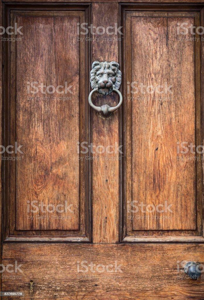 Antique Lion Door Knocker on Wooden Door stock photo