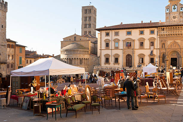 Antique Market of Arezzo in Tuscany Arezzo, Italy - December 31, 2011: Tourists and locals at the monthly antique fair held in the main square of Arezzo. The building in the middle between the two churches is the city\'s law courts. piazza grande stock pictures, royalty-free photos & images