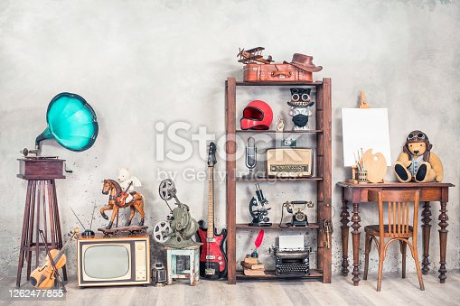istock Antique media devices, writers tools, gramophone, film projector, old Teddy Bear toys and white canvas blank on easel, violin and guitar front concrete wall background. Vintage style filtered photo 1262477855