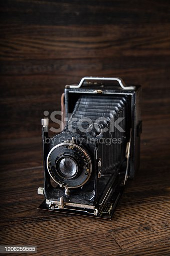 old antique medium range camera against a dark wood background