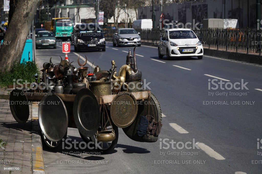 Antique metal objects on wheelbarrow at road with vehicles stock photo
