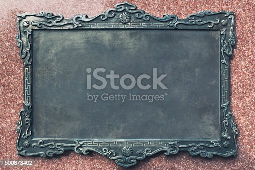Closeup photo of an antique blank metal plaque on granite wall.