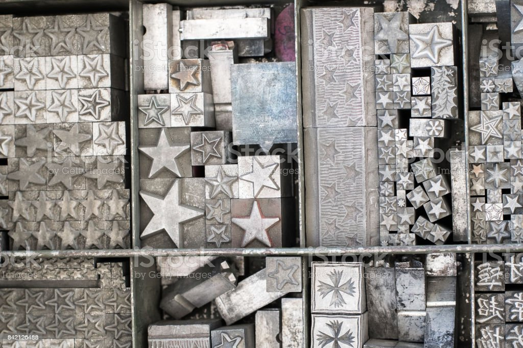 antique metal typeset stars in a printers drawer at an antique flea market forming a pattern in military symbols and colors with room for copy stock photo