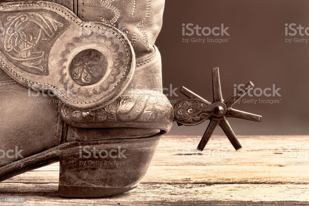 Cowboy boots and Mexican spurs in black and white sepia tone with...