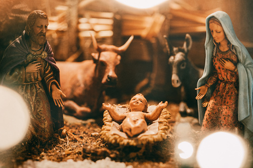 An old Christmas nativity set, with Joseph, Mary, and the baby Christ child in a manger.  Animals and visitors also visible in the classic scene.  A warm holiday background.