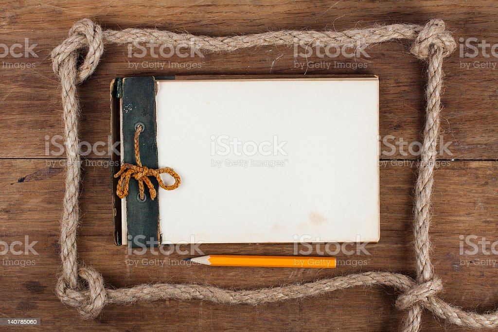 Antique Notebook (1940th) and pencil in rope frame on wood royalty-free stock photo