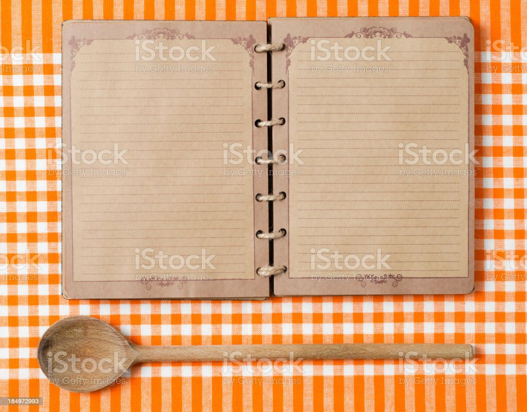 Antique notebook and wooden spoon on orange tablecloth Wooden spoon and old notebook on orange tableclot. Blank Stock Photo