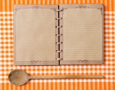 Antique Notebook And Wooden Spoon On Orange Tablecloth Stock Photo - Download Image Now