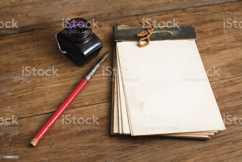 Antique notebook, ink pen and inkstand on wood royalty-free stock photo