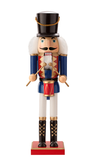 Antique Nutcracker Drummer with a red drum. He has white hair and beard. He sports a black hat, with a blue coat and black boots. The point of view is straight on, and is isolated on a white background.