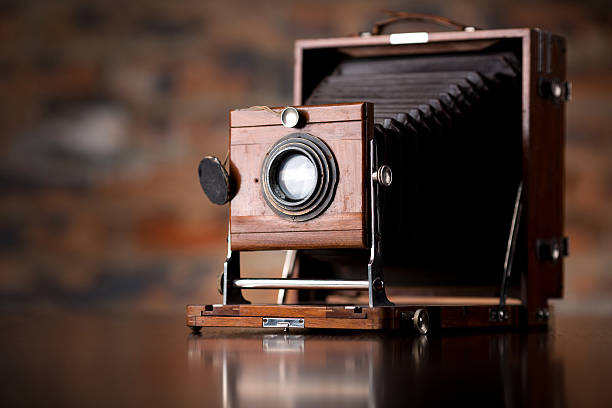 antique old photo camera on wooden table - camera photographic equipment stock photos and pictures