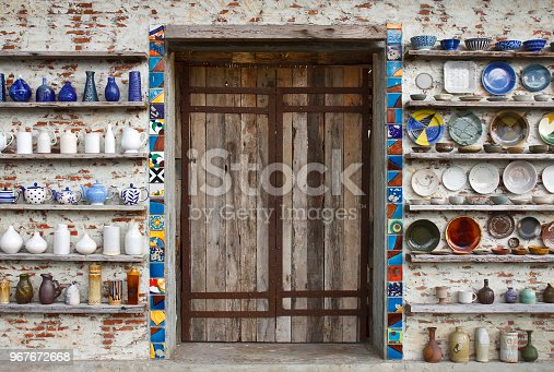 istock antique old wood door with cup jar flowerpot dish and bowl vintage and retro on the old wooden shelf and white brick wall for home and restaurant interior or exterior architecture decor background 967672668