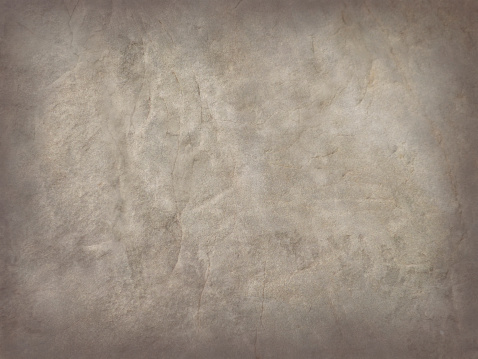 A rough textured beige, gray and brown grunge antique paper abstract architecture background. The weathered surface is lighter beige and gray, increasing to a darker brown border.