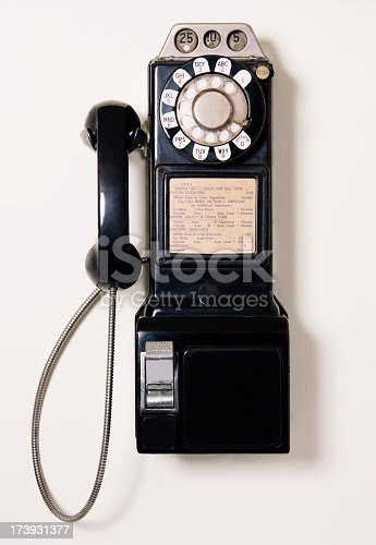 antique coin operated pay phone on wall