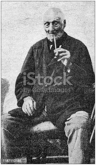 Antique photo: 100 years old man smoking pipe
