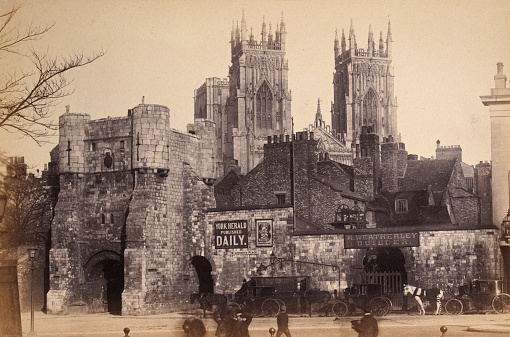 Antique photograph of Bootham Bar and York Minster, York, Yorkshire, England, 1880s, 19th Century, Advert for York Herald, R Weatherley Builder's yard, Horse and carriages, people walking in the street