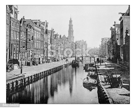 Antique photograph of view of a Canal in Amsterdam (Netherlands) as it appeared in the 19th century, with boats, typical houses with their stepped gable façades overlooking the street and the canal, and with the high tower (Westertoren steeple) of the 17th century Renaissance style church called Westerkerk. The 17th-century canals of Amsterdam are on the UNESCO World Heritage List