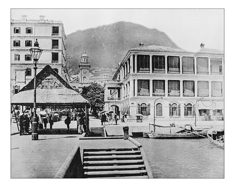 Antique photograph of English buildings in Hong Kong (China) during the 19th century, mixed with local elements.