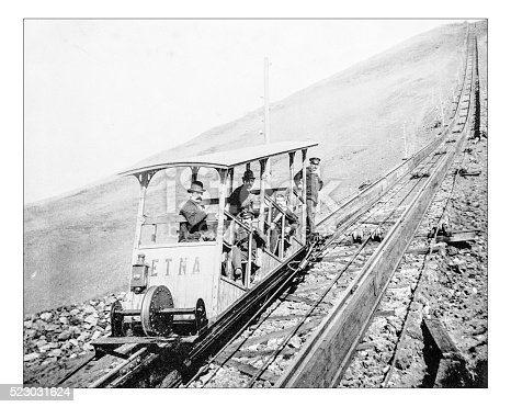 Antique photograph of ascent of Mont Vesuvius by funicular railway during the 19th century. The railway was built after 1878 to connect Ercolano (Naples) to the area just below the crater of Vesuvius Volcano. In the picture one of the two coaches, the one called Etna (named after the other famous Italian volcano), with its passengers and the driver. Behind them the rails go up towards the top of the mountain (19th century Stereoscopy