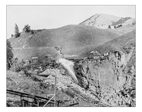 Antique photograph of placer mining scene (mining of stream bed deposits for minerals/gold by water pressure) in California (Usa) during the 19th century. The scene is set in a Californian valley