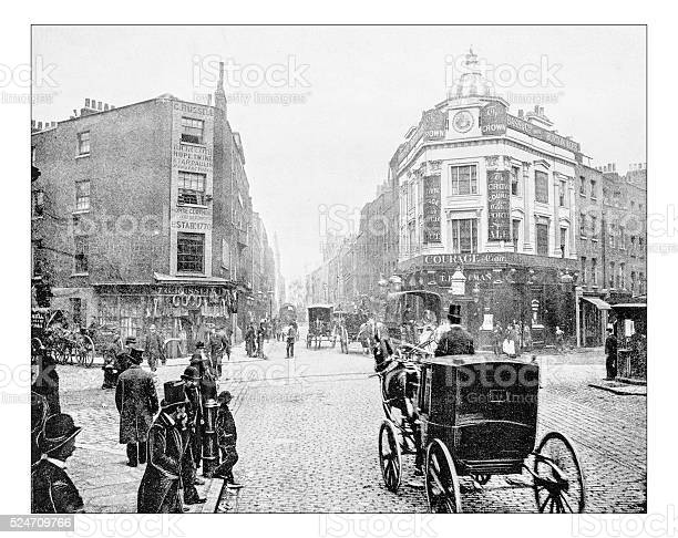 Antique photograph of Seven Dials junction in London as it was in the late 19th century. It is a small circular square, a road junction of seven streets in Covent Garden in the West End of London. In the picture the square, busy with people and carriages, with its buildings with pubs and shops of a district tha was quite poor (now it's a fashionable shopping district).