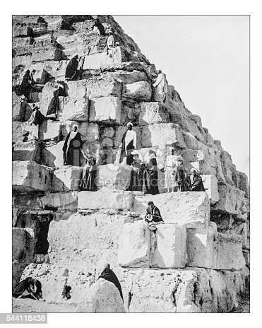 Antique photograph of 19th century tourists ascending the Great Pyramid of Gyza together with some Bedouins.The Great Pyramid of Giza (or Pyramid of Khufu or Pyramid of Cheops) is the largest of the Giza pyramid complex (El Giza, Egypt)