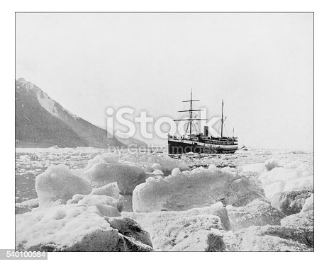 Antique photograph of of a vessel sailing in the Glacier Bay Basin (Alaska, USA) during the 19th century. In the picture the surrounding mountains and glaciers and the ship breaking the ice in the freezing waters of the Ocean, surrounded by ice plates and small iceberg
