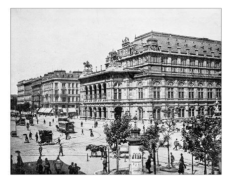 Antique photograph of view of the Ringstraße with the Vienna State Opera (Wiener Staatsoper) during the 19th century (when it was called Imperial Opera House or Vienna Court Opera). The monumental 19th century theatre is an opera house built in the Neo-Renaissance style. In the old photograph also other buildings overlooking the Ringstrasse and the promenade itself, busy with people, carriages and horse-drawn wagons