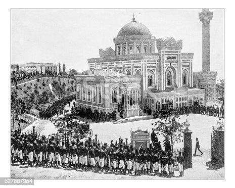 Antique photograph of the Yıldız Hamidiye Mosque or Yıldız Mosque (Istanbul, Turkey) in a photograph of the late 19th century, with its surroundings during an Ottoman state ceremony with a military parade. It is an Ottoman imperial mosque located in Yıldız neighbourhood of Beşiktaş district and built upon request of the Ottoman sultan Abdul Hamid II between 1884 and 1886. The mosque was intended as a private mosque for the sultan.The building, in a mix of  Neo-Gothic style and classical Ottoman motifs, features a rectangular plan, a minaret